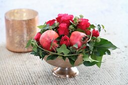 Festive Christmas arrangement of roses, pomegranates and ivy tendrils
