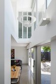 View from hallway into double-height living area with terrace windows