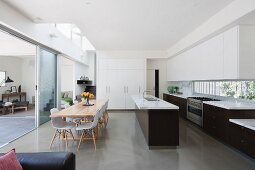 Dining area in open-plan, designer kitchen and view through open glass sliding door into living space