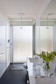 Timeless bathroom with white marble washstand counter, black tiled floor and shower area