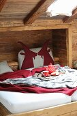 Red felt animal motifs on bed headboard in rustic bed niche