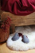 Grey felt slippers on white sheepskin rug under rustic wooden bed