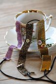 Three hand-woven bracelets with glass beading draped over gold-rimmed teacup