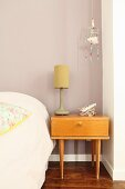 Table lamp on retro bedside table below pretty dreamcatcher