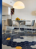 Runder Designertisch mit filigranen Stühlen auf Wabenfliesenboden