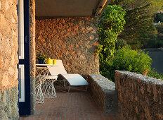 Liege und filigrane Outdoormöbel auf mediterranem Balkon