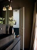 Offene Kassettentür im Bad mit schwarzem Waschbecken