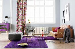 Living room with leather sofa, purple rugs and purple sideboard