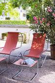 Zwei rote Liegestühle mit Fußhockern auf sommerlichem Kiesplatz