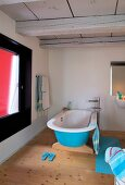 Blue free-standing bathtub in bathroom with wooden floor and wood-beamed ceiling