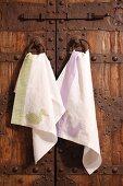 Hand-made tea towels hung on wooden door