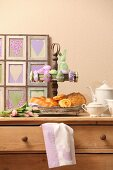 Pastries on vintage cake stand and Easter ornaments on top of chest of drawers