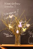 Easter arrangement in glass vase on wooden table against chalkboard with chalk messages