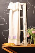 Pastries, carafe, vase of tulips and vintage window frame with curtain against chalkboard wall