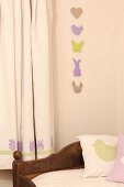 Garland of Easter motifs on wall next to curtain with tulip motifs