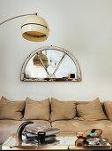 Wandspiegel im Rahmen eines Bogenfensters über dem Sofa