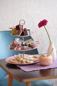 Wrapped sweets on cake stand, Gerbera daisy and sugar bowl on table