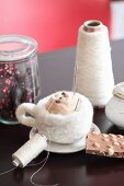 Needle-felted a cup of cappuccino, chocolate, sugar bowl, Gerbera daisy, yarn and glass jars on table