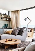Upholstered sofa, standard lamp, round wooden table and shelf in the living room with sea view