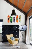 Black metal locker cabinet with colorful skateboards on the wall, yellow armchairs and photo lamp in front of the patio door