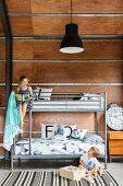 Bunk bed with metal frame and siblings in the children's room with wooden paneling