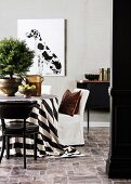 Conifers on table with black and white tablecloth, chairs, black sideboard and picture with Dalmatian motif on the wall