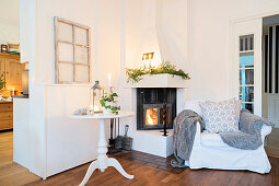 Comfortable armchair and side table in front of lit fire