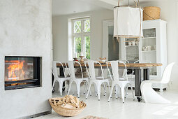 Long table in pale dining room with fireplace