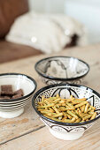 Snacks in three bowls with black and white patterns
