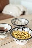 Drei schwarz-weiß gemusterte Schalen mit Snacks