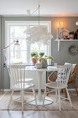 Windsor chairs and wicker chair at round table in dining room