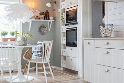 Round table in white country-house-style kitchen-dining room