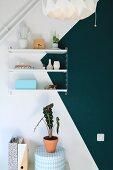Regal an weisser Wand mit petrolfarbenem Dreieck