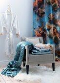 Grauer Polstersessel mit Bettwäsche und glänzender Tagesdecke vor Vorhang mit Engelsmotiven, an Wand Kimono im Ankleidezimmer