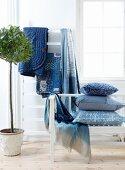 Kissen, Decken und Wohntextilien in Blautönen im Schlafzimmer, seitlich Zimmerbäumchen