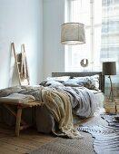 Doppelbett im Schlafzimmer mit sandfarbenen Textilien und Treibholz Accessoires