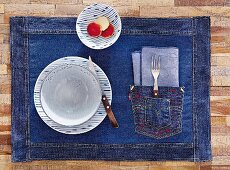 A denim placemat with patch pocket and red stitching