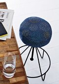 A stool with the seat upholstered in denim and decorated with embroidered spirals
