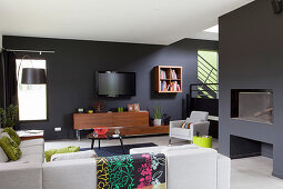 Fireplace, sofa, coffee table, sideboard, wall-mounted TV and armchair in living area with dark walls