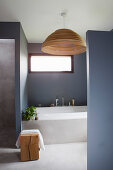 Bathtub and window in bathroom with grey walls