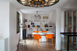 Stained-glass ceiling light and dining table with orange chairs in background