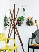 Various ethnic animal masks decorated with flowers and coat stand made from wooden props between armchairs