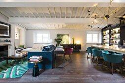Blaues Polstersofa vor Kamin und langer Tisch mit Schalenstühlen in offenem Wohnraum mit weisser Holzbalkendecke