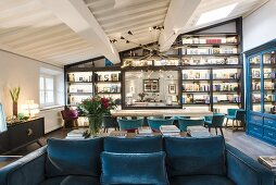 Blue sofa, long table, shell chairs and wall covered in shelves in open-plan interior