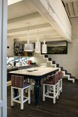 Bar stools with graphic patterns on upholstery around tall, elegant dining table below ceramic lamps