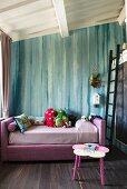 Rosa Bett mit Kuscheltieren vor türkisfarbener Wand im Mädchenzimmer, seitlich Leiter an Hochbett