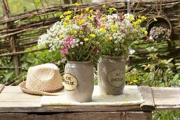 Bouquets of wild cow parsley, red campion and buttercups in two stone jars on garden bench
