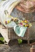 Bouquet of cow parsley, red campion and buttercups and swing-top bottle with wild-flower wreath in wicker basket