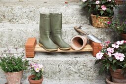 Wellington boots and plant pot on DIY cane shoe rack on stone steps