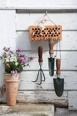 Garden tools hung from canes in brick